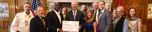 Group of people with the governor receiving a large check